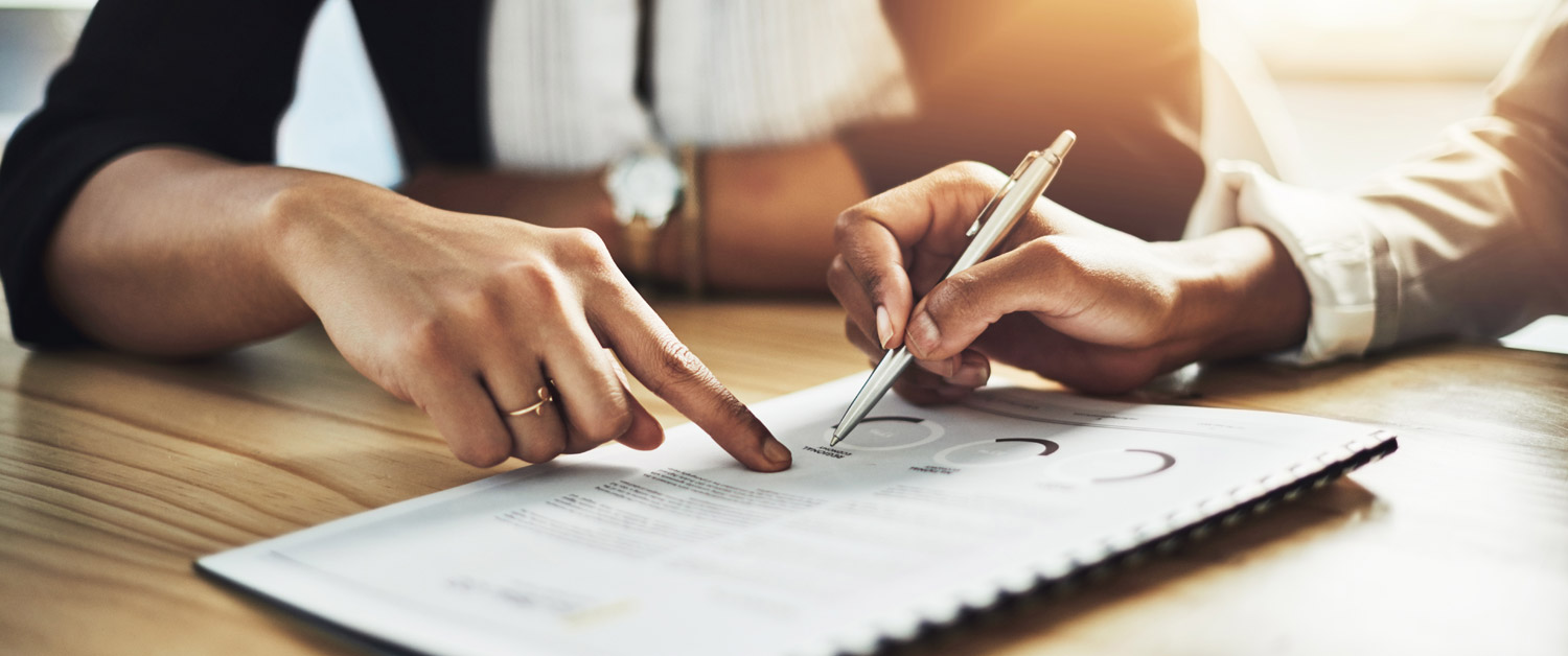 two people using pens to point to a word on a piece of paper